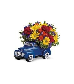 Teleflora's '48 Ford Pickup Truck Bouquet - Orange roses, red carnations, yellow daisy chrysanthemums, purple statice and more are all delivered in a terrific truck that just happens to come with its bed full of flowers.