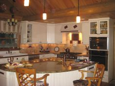 We love the design of this Ward log home Kitchen with its white cabinets.