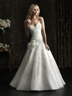 Allure Bridals Style No. 8962. Soft and romantic in lace. This fitted ball gown has a strapless, sweetheart neckline. Lace appliques continue throughout the entire design as soft, flowers accent the dropped, asymmetrical waistline. Covered buttons and a chapel length train complete the style.