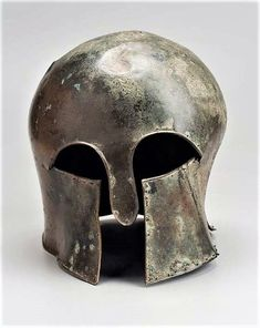 Corinthian type helmet, flexible cheek guards, & two eye openings on either side of a long nose guard) appears to have been severely battered by blows, probably during battle. Fairly cylindrical shape is typical of earlier Corinthian helmets.The pins inserted into holes along the edge of the helmet were attachment points for a leather lining, Circular hole in nape guard may have resulted from the attachment of the helmet to a post in the sanctuary, a typical method for displaying votive…