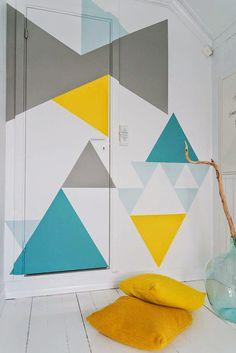Une œuvre géométrique à cheval sur la porte et le mur