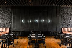 This modern restaurant features an open plan dining room, with dark colors and natural materials, like wood, leather and stone. #ModernRestaurant #RestaurantDesign