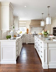 Elegant kitchen features a pair of cylinder pendants illuminating an ivory island topped with gray quartzite.