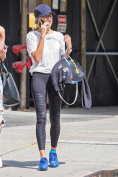 Hailey Baldwin wearing Alo Yoga Athena Moto Full-Length Sport Leggings, Saint Laurent Small Rive Gauche Colorblock Satchel, James Perse Scuba Trucker Hat in Dark Navy and Nike Air Max 90 Hyperfuse Sneakers in Photo Blue
