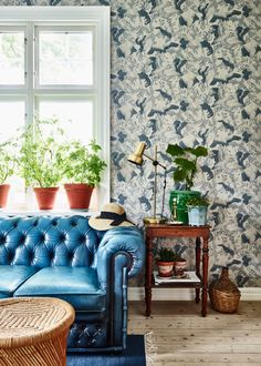 blue and white wallpaper with a blue leather tufted sofa in the living room | swedish house tour on coco kelley