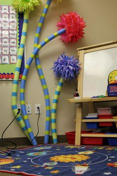 DIY Truffula Trees using pool noodles, construction paper, and tissue Pom-Poms