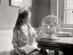 "The Naturalist, Washington, D.C., circa 1915. ""Child with birdcage."" A budding Audubon with her notes."