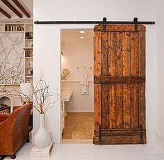 """Small bathrooms rooms are frequently constructed with little room for a standard swing door. (I know because I have one).  The Brooklyn Home Company's rustic wood plank door and black track is striking against the white wall.  This style door is perfect for powder rooms placed in main living areas and solves the pesky design quandary we often hear: """"How do I hide the bathroom?!"""" Closed, the door looks more like a textural element complimenting wood ceiling beams than an entry to the loo."""