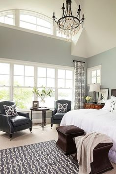 Pale blue-grey walls, white cathedral ceilings, black wrought-iron anf shell chandelier. ....i love that heavy dark chandelier, especially withbthe white&beige shells hanging from it instead of beads or crystal.  Black leather chairs. Black, grey, white bedroom.    Palmer Pointe Road Residence by Martha O'Hara Interiors