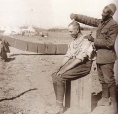 WWI: A Turkish prisoner earns his keep by cutting an Anzac's hair.