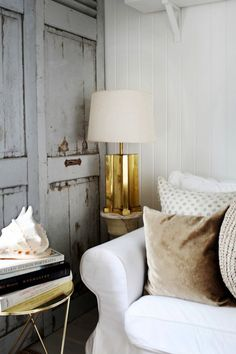 Chic cottage living room features white beadboard walls framing white slipcovered sofa with rolled-arms accented with brown velvet pillow next to antique brass lamp next to gray distressed doors. Cottage Living Rooms, My Living Room, Home And Living, Living Spaces, Coastal Living, Coastal Decor, Apartment Living, Distressed Doors, Le Logis