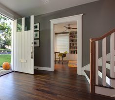The bright white baseboard and trim provides a nice contrast between the deep gray walls and the dark hardwood flooring.