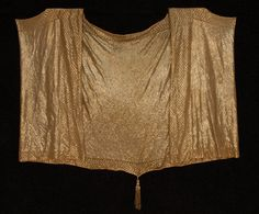 HEAVY ASUITE CAPE, c. 1920. Ecru cotton net almost completely covered in silver metal staples, bordered in a diamond and chevron pattern, the center back having a gold metallic tassel at hem