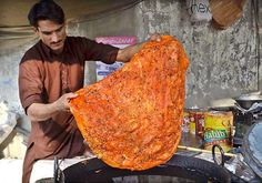 A PARATHA ( Bread made from dough), and added with spices and herbs being prepared . Lahore.