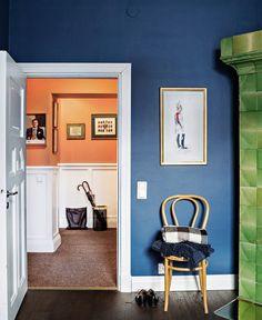 Eri huoneiden seinien sävyt on mietitty sopimaan yhteen. Vihreä kakluuni, sininen makuuhuoneen seinä sekä eteisen ja galleriakäytävän oranssi seinä muodostavat värikkään, mutta harmonisen kokonaisuuden. Viltit Gant ja sateenvarjoteline Svenskt Tenn.