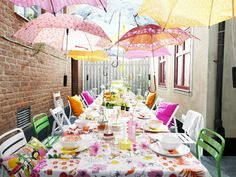 Create a fun canopy of umbrellas and mix and match fabric and serving ware in bright, fun colors for an outdoor party that's sure to welcome the season.
