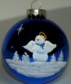3 1/4 inch Midnight Blue Glass Ornament Hand painted with a Peaceful Angel Snow person. Under the Angel is a glistening snow fall. Beside the