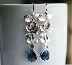 Beautiful matte silver blue sapphire teardrop glass pendants and matte silver triple orchid flowers dangling from sterling silver french ear