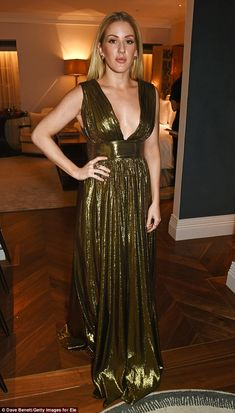 Golden goddess: The striking singer sported a gold lame DHELA gown with a plunging neckline