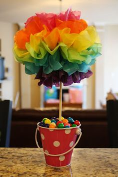 Colorful tissue pompoms with gum balls or even colorful marbles for centerpieces. Mom's already a pro at those tissue pompoms