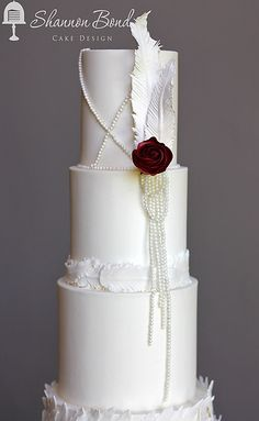 Vintage Feather Wedding Cake by Shannon Bond Cake Design in Olathe, Kansas. Hand cut sugar feathers, sugar roses and edible fishnet lace with strands of edible pearls. A vintage cake design with a modern wedding twist! www.sbcakedesign.com