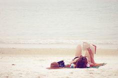 Sunbather reading a book on a beach
