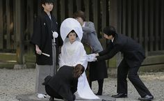 27/jan/2013 - JAPAN - Noiva é ajudada com seu traje de casamento tradicional para fotos com seu noivo (à esq.) logo após seu casamento em santúario em Meiji Shinto, Tóquio. By FSP.