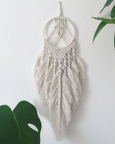 This macrame dream catcher is made of cotton and a wrapped silver craft frame. This modern bohemian macrame dream catcher with 7 macrame feathers looks great, from the ceiling or the wall, over your bed or in a window. The length is 52 cm and the widt Macrame Wall Hanging Patterns, Wall Hanging Crafts, Macrame Plant Hangers, Macrame Patterns, Macrame Design, Macrame Art, Macrame Projects, Modern Macrame, Modern Bohemian