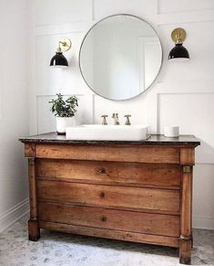 Design By: Courtney Dickey and TS Adams Studio The shiplap frames this beautiful coastal bathroom, but the vintage style sconces with the blown glass globes are a gorgeous detail. Classic White with G #coastalstylebathroom #vintagebathrooms