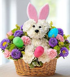 """Hoppy Easter: Every dog has its day, but Easter belongs to the bunnies! We've dressed up our truly original a-DOG-able arrangement, adding pastel carnations, asters and poms to a gathering of fresh white carnations. Wearing a pair of playful bunny ears and accented with colorful eggs, this cute creation will surely make their holiday celebration """"hoppy!"""" #holidays #floral #bouquets #flowerarrangements #beautiful #nancysfloral #love #flowers #Gresham #Oregon #flowerpower #Easter"""