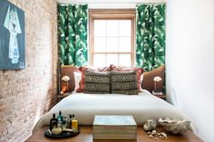 Banana leaf print drapery with a live edge wooden headboard and mudcloth patterned pillows.