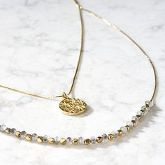 """A double chain for double luck. A single strand of delicate glass beads hangs below a second shorter chain and brass medallion pendant. Artisan partner, Tara Projects, works to change the lives of India's """"untouchables"""" by eliminating unfair trade practices and child labour. This necklace's length can be extended for more flexibility."""