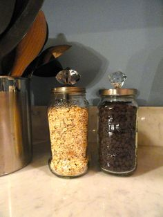 Repurposing: Spaghetti jars into pretty storage containers. Just paint lid and screw a doorknob in it.