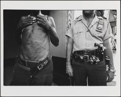 """Leonard Freed, The drug pusher showed his knife wounds from past battles, """"I'm still alive,"""" he said. The police officer replied, """"You can never have enough fire power."""" New York City, 1978. © Leonard Freed — Magnum Photos / Museum of the City of New York"""