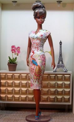A figure hugging sheath dress in a lovely Chinoiserie patterned cotton with hand beaded details. The print of the fabric depicts peacocks in an Asian garden filled with bamboo and colorful flowers in shades of lime, orange, turquoise and bright pink. The neckline is slashed, resulting in a modified V. The elegant peacock that is featured on the front of the dress sparkles with beads. The sheath is fully lined in lime green silk. This fashion fits most 1/6 scale fashion dolls.