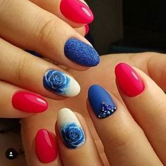 A brightly colored rose nail art design. The nails are painted in hot pink and blue polishes respectively. On one of the nails the roses are painted in blue while it has a white background and other nails have embellishments added to them.