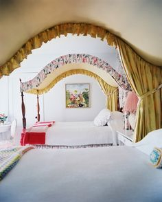 Sister Parish - A pair of arched floral canopy beds dressed with white linens