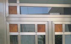 2006 Puerta Sánchez Blázquez en Moratalla. Detalle de la puerta, diseñada por Ernesto Oñate, donde se aprecia la utilización de los materiales, (acero, cristal y Palo Rojo) con los cuarterones en punta de diamante de madera de Palo Rojo.