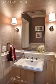 Grasscloth wallpaper in powder room. Thomas Obrien Bryant sconces, West Elm metal mirror