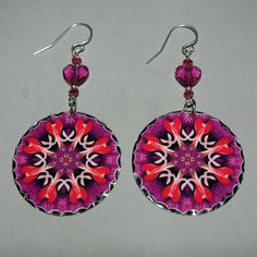 Earrings adorned with my pink bleeding heart boho chic mandala new age sacred geometry hippie kaleidoscope charm titled That's Amore. <br /> <br />These heart earrings are lightweight and dainty. Heart earrings begin with a dangle of Indian pink bicone Swarovski crystals and fuchsia heart Swarovski crystal beads that accentuate the colors in the mandala charm that ha...