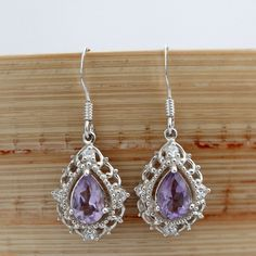 Handcrafted to be high quality, these pear drop earrings feature amethyst gemstones in a classic design. The intricate sterling silver hardware border brings out the beauty of the stones.
