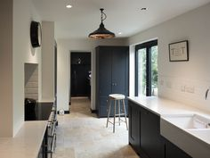 We love this image sent into us by a customer. Our Country Mix Tumbled Travertine with a pantry blue kitchen from deVOL Kitchens