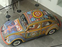 """The Vochol is a Volkswagen (VW) Beetle that has been decorated with traditional Huichol (Wirrárika) beadwork from the center-west of Mexico. The name is a combination of """"vocho"""", a popular term for VW Beetles in Mexico, and """"Huichol"""", the common name of the Wirrárika indigenous group"""