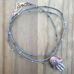 "Clay Hamsa, evil eye on long, gray, braided, beaded cotton cord necklace. Cotton braid color is gray. Silver and neutral accent beads used along length of necklace. Hamsa is glazed in multicolors and has ""evil eye"" detail. I have handmade the sterling silver clasp as well.  Length is 32.5 inches   To return to Mii Myx Jewelry Studio ETSY homepage click https://www.etsy.com/shop/MiiMyxJewelry?ref=hdr_shop_menu"