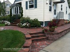 Curving brick walkways with retaining walls are an elegant way to lead visitors to both entry porches. Landscape by Lisk Landscape Management via Front-Porch-Ideas-and-More.com
