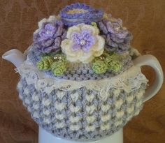 this pretty cosy is shabby chic and knitted to my own pattern and design, in soft double double knitting in shades of soft grey and wool rich cream with parma violet, lilac and lavender accents....it is knitted in lovely bee stitch with stocking stitch top .... it measures 13.5 inches by 6.5 inches and is a lovely fit for a standard, round 2 cup tea pot.....soft and thick, it keeps tea nice and hot.... the cosy has carefully sewn cream cotton broderie anglaise lace and is decorated with…