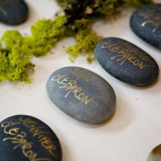 The couple played up their organic theme by using dark gray river rocks as escort cards. They wrote each guest's name on the stones with metallic gold ink. from the album: Amber & Josh: An Outdoor Wedding in Breckenridge, CO Wedding Table, Wedding Favors, Wedding Decorations, Wedding Reception, Brunch Wedding, Trendy Wedding, Our Wedding, Wedding Ideas, Wedding Band