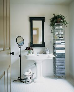 That wirework towel stand though!  In a bathroom with bright-white tile and porcelain fixtures, few accessories are required. The carved wooden wall mirror was painted a dark gray-black; the standing adjustable mirror and the wire wastebasket did not need painting. Neither did the tall, wirework towel stand, one of a pair that Martha found at an antiques show.Get the look with Martha Stewart Living Larsson Carbon Black Mirror at the Home Depot.Order the Larsson Carbon Black Mirror