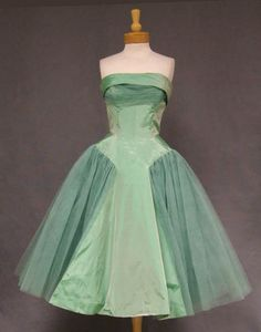 ~1950's prom dress in iridescent mint taffeta and tulle, Cuffed, strapless bodice with pleated tulle bust overlay and pointed waist. Bow with sash at rear neckline. Multi layered tulle skirt with pellon backed taffeta panel. Skirt is sheer but comes with it's own matching acetate lined  Rear metal zipper. Bodice is lined in marquisette and boned~