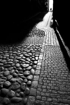 Sun and shadows accentuate the many different textures created by the rocks and bricks used to create this road